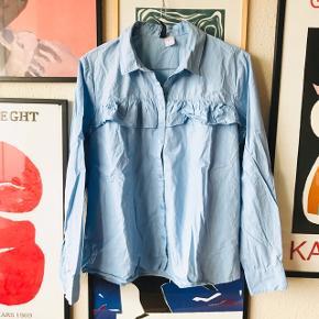 Pæn skjorte med flæser fra H&M i str. 38 🌷 brugt to gange, men desværre købt i forkert størrelse. Standen er som ny! Har flæse foran på brystet og bagpå på ryggen ☀️  Bemærk - Sendes med DAO (33kr), bytter ikke og sender ikke billeder med varen på ⭐️☺️