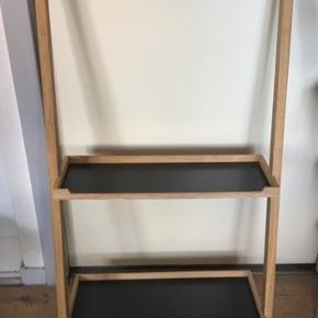 SkagerakNomad Reol Nomad fra Skagerak (Trip Trap) er et åbent og fleksibelt opbevaringsmøbel. Møblet læner sig op ad væggen hvilket gør den let og flytbart.   Materiale = Eg  Mål = BxDxH = 55x3,5x110 cm Dybde på hylder = 19/25 cm. Inkl. 2 hylder og 4 kroge  Afhentes i Odense.