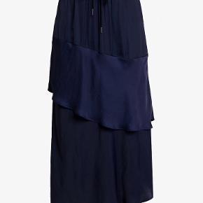 Smuk nederdel fra Six Ames med bred elastikkant i taljen og bindebånd, flæser og asymmetrisk facon, der falder flot. Nederdelen kan bruges både til hverdag med sneakers og til fest med høje hæle og fin top