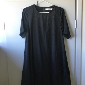 Sort løs kjole med diskrete prikker