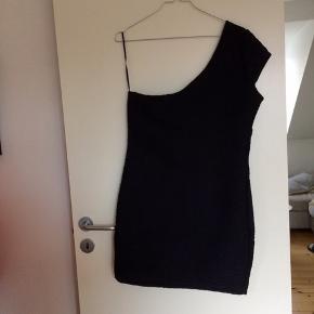 Sort kjole med diskret mønster i stoffet. One-shoulder-model i lækkert strækstof.