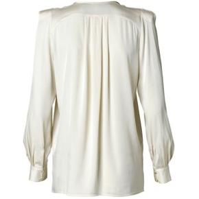 Fantastisk smuk bluse i beige/råhvidt silke-agtigt stof. Jeg har fjernet skulderpuderne, så den sidder som en normal skjorte. Kan sende dem med ved køb, de kan nemt sys på igen.  Ingen fejl og er SÅ FLOT.  Sælger den også i sort.