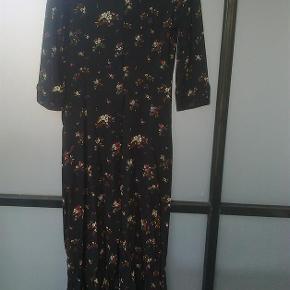 Varetype: maxi kjole med blomster maxikjole Farve: Brun  Kjole med knapper hele vejen ned foran.  100 % viskose Sendes forsikret med dao mm andet aftales