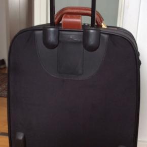 Rummelig trolley kuffert med indvendig lynlås rum og 2 udvendige. Cognac farvet læder og kombinationslås. L.44 cm.B 21 cm.H60 cm.