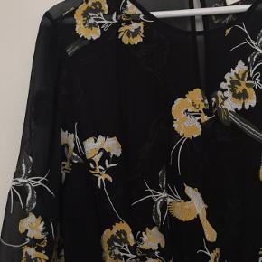 Smuk kjole med med hvidt og gult blomstermønster, som er broderet på. Elastik i taljen og ved håndleddet.  Brugt få gange. Underkjole medfølger ikke. 100% viskose