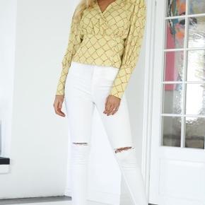 Super fin bluse fra Birgitte Herskind.  Blusen er gul med smart print. Den har slå om effekt og er meget elegant med de fine skuldre og v-hals udskæring. Den lukkes i siden med fine knapper.  Style den med en nederdel eller et par bukser med vidde.  Helt ny og med mærke på endnu, er i butikkerne nu nypris 1600,-