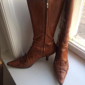 Fede vintage stilet støvler i cognacfarvet kernelæder med indvendig lynlås. Hælhøjde 7cm, total højde 36cm. Str.40...Super fed støvle... købt hos Birger Christensen i Kbh. for ca 20 år siden.... fin vintage stand, ny sålet...har ligget opbevaret de sidste ca 8år...nyprisen er 4000,-kr....original æske og dustbag medfølger... pris inkl. Porto DAO... gerne mobilpay
