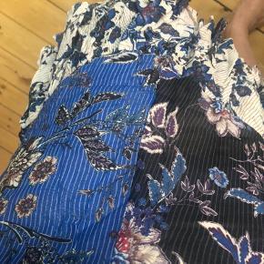 Vildt fin nederdel i blåt blomstret print. Den har en lille fejl ved syningen ved lynlåsen, men ikke noget der hverken kan ses eller mærkes.