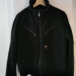Boss Orange, kort sort uld jakke med Rib kant ved ærmer og forneden.  Intet slid, eller huller. Trænger til en rens ellers fuldstændig fin og brugbar.