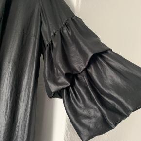Smuk kjole i shiny sort med bindebånd og underkjole. 'Ballon'-ærmerne falder super flot.
