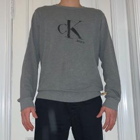 Rigtig fed jumper fra Calvin Klein jeans. Den kan virke lidt stor, men har elastik i ærmer og livet, hvilket gør at man kan bruge den som en afslappet sweat. Trøjen er brugt flere gange, men bærer ikke tydelig tegn på brug og er generelt i god stand. 7/10😃