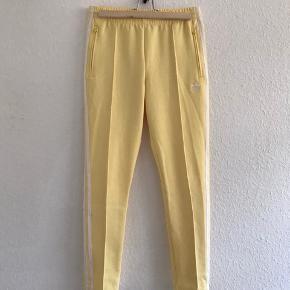 Lyse gule Adidas Originals pants.   Der er lynlås i siden i benene og snøre i livet.   På det sidste billede kan I se, hvordan de sidder, hvis man er 176 cm 💁🏼♀️