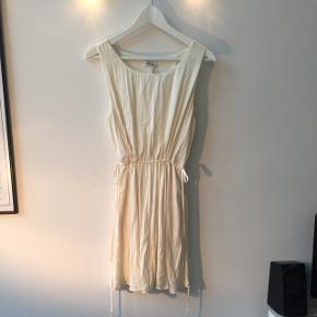 Råhvid kjole med bindebånd i siden.