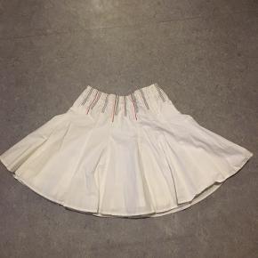Hvid nederdel med røde og blå detaljer øverst. Fejler intet.
