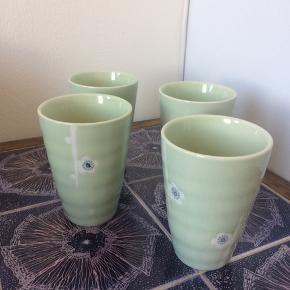 4 keramik kopper / krus Smukt malede med hvide blomster og glaseret i lys grøn med skinnende finish Fra Tiger - købt for 25 kr. stk Brugt en håndfuld gange Fremstår som nye 11,5 cm. høje  Alle varer under 500 kr.: Køb 3, få den billigste gratis!  Krus // the // kop // kinesisk // asiatisk // keramik