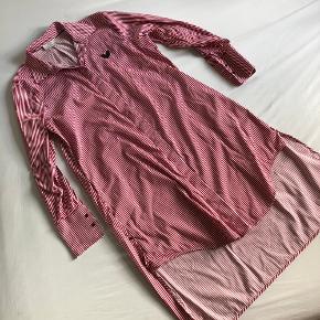 Stribet bomuld skjortekjole af Rika Studios. Den har skjulte knapper og to lommer.  Længde Foran 90cm Bagpå 110cm