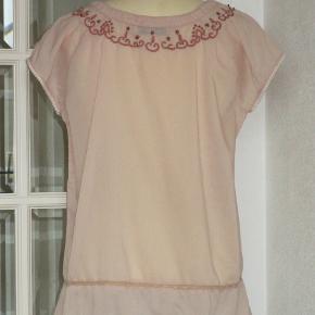 100 % NY: Feminin gl.rosa bluse med blonde, broderi og perler. Materialet er bomuld.   Brystvidde: 56 cm x 2 Hoftevidde: 57 cm x 2 Længde: 69 cm  Ingen byt, og prisen er fast