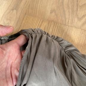 Skøn buksedragt i silke fra Storm og Marie. Lynlåslukning bagpå og læg ved skuldre. To forlommer og længde til midt på låret. Brugt men virkelig pæn