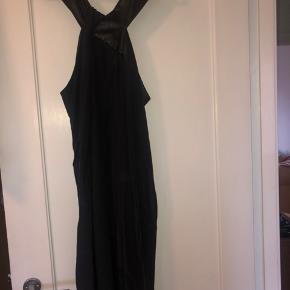 Fin detalje ved halsen, med kryds af kjolens stof og læderlook