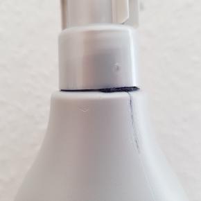 Ny og ubrugt 980 ml shampoo. Da låget har været skruet skævt på, er der løber en lille smule ud ved låget, se foto 2