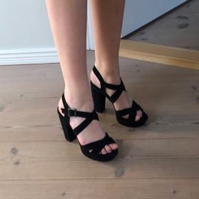 Sorte høje hæle med plateau og chunky hæl. De er kun brugt 1 gang og der er derfor ingen tegn på slid. Materialet er ruskindslook