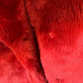 Faux fur jakke i rød, kun brugt en enkelt aften.  Mærket er klippet ud i nakken og har desværre efterladt et lille hul i foret.