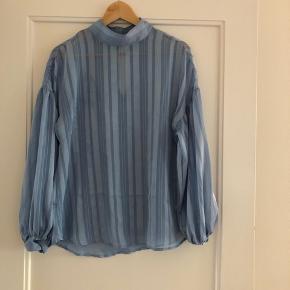 Flot lyseblå gennemsigtig skjorte med høj hals og løse ærmer.