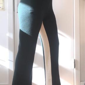 Track pants/træningsbukser i 100% merino uld strikket kvalitet, derfor meget fleksible  Elastik i taljen og lige ben Mørkegrønne med hvid panel indvendig, højtaljede  almindelig brugsspor, ingen fejl eller skader.  mål:  talje: 36,50cm - 56cm skridtlængde: 38cm indvendig benlængde: 69cm