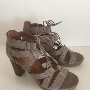 Flotte sandaler fra det lækre mærke Poul Green, som laver sko som er meget behagelige at gå i. De hedder str. 3,5 som ligger mellem 36 og 36,5 men jeg synes de er store i størrelsen og har beskrevet dem som 36,5. Sandalerne har 9 cm. Hæl og 2 cm. Forfodsplateu, men man kan ikke mærke man kommer op på 9 cm, de er meget behAgelige at gå i.  Sandaler Farve: Lys Brun Oprindelig købspris: 1349 kr.