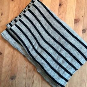 Lækkert varmt tube tørklæde, 50% uld i grå med blå striber.  Det er løbet en lille smule, et enkelt sted se billede 3. Dette er dog ikke noget man ser når det er på, ellers fejler det ikke noget