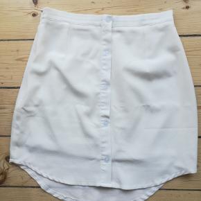 Nederdel, str. 36, Missguided, Cremefarvet hvid, Næsten som ny Sommerlig og enkel, feminin nederdel med for. Den har lynlås i siden og knapper foran. Den er i et let elastisk materiale: 95% polyester og 5% elastan. Længde foran: Cirka 44 cm. Længde bag: Cirka 48 cm. Den er brugt én gang og vasket én gang. Nypris: Cirka 250 kroner. Eventuel fragt lægges oveni: 37 med DAO til nærmeste posthus/butik. Foretrækker betaling over mobilepay, da jeg gerne vil være fri for gebyrer :-)