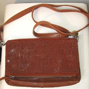 Varetype: Superlækker clutch/taske Størrelse: Se mål Farve: Brun Oprindelig købspris: 999 kr.  Superlækker clutch/taske - to-i-en. Remmen kan tages af.  Inden i tasken er der et stort, et lynlåsrum + to mindre lommer. Der er lomme øverst i tasken + bagerst  Mål: Bredde: 28 cm Højde: 19 cm Omkreds rem: 97 - kan reguleres  Bud fra kr 400 pp - porto er sat til forsendelse via DAO, andet kan selvfølgelig aftales.  Respekter venligst, at jeg ikke bytter - og at jeg ikke svarer på forespørgsler om dette.  Kan afhentes København, Østerbro  Betaling via bankoverførsel eller TS  Yderligere info: klik på mit brugernavn og derefter på beskrivelse.