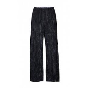 Helt nye bukser i mærkeligt zhenzi og str er small dette er stor pige str. De svarer til str 42-44. Bukserne som er 100% polyester er sorte med glimmer. De har vidde i benene dg er meget lange. De er til at mam kan  sy dem  op.