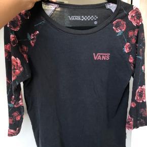 Lidt edgy sort Vans bluse med trekvarte ærmer med roser på ærmerne og Vansmærket trykt på brystet Købt i Vans butik i USA