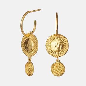 IMANI EARRINGS  Imani amuletøreringene er en skat i sig selv. Mønterne har en let bevægelighed og et rent udtryk der gør dem til de perfekte hverdagsøreringe.  Højde: 37 mm Pris: 650 DKK, prisen er for et par.  Materiale: Sterling sølv (925) belagt med 18 karats guld.