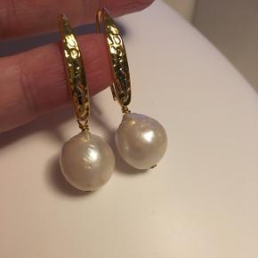 Ørekroge i forgyldt sølv med stor ferskvandsperle. Længde ca 4 cm. Perlene kan variere lidt i størrelse og udseende. Mål på selve perlen er ca 14-16x14-16mm  Flere par haves og prisen er fast og ikke til forhandling. Kan afhentes eller sendes mod betaling.