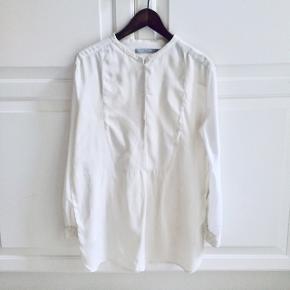 Smukkeste silkemix skjorte med lidt længde og med små changeringer af Hvidt i Hvidt. Tuxedo-look. Str 38 og meget størrelses-svarende. Kun vasket på Silke/skåne vask. Nypris 1199