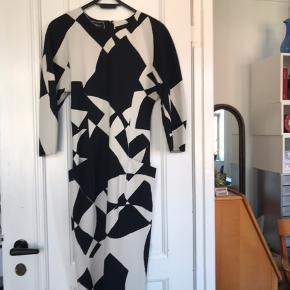 Elegant og feminin kjole med fine detaljer.  To lommer og en slids med lynlås bagpå.  Jeg købte den herind sidste år, men den viste sig at være for lille til mig.  Hvis den ikke var det ville jeg aldrig af med den! Så den har hængt i mit skab hvor jeg har frydet mig over hvor smuk den er.  Nu skal den videre til én der kan bruge den! Kan desværre ikke tage billeder med den på, fordi den som sagt er for lille til mig.