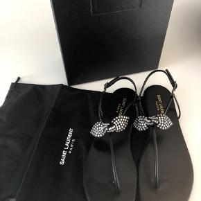 """Varetype: Smukke sandaler - aldrig brugt Farve: Sort Oprindelig købspris: 3375 kr.  Smukke sandaler - model """"nu pied studded bow"""". Aldrig brugt - kun prøvet på. Æske, dustbag medfølger om man vil. Flotte på foden med en helt flad hæl (ca 10 mm).   Købt (af mig) i Saint Laurent butikken i Illum.   Nypris DKK 3.375.  Bud er velkomne - køber betaler Porto (sender via Dao) og ts gebyr men jeg handler gerne via mobile pay."""