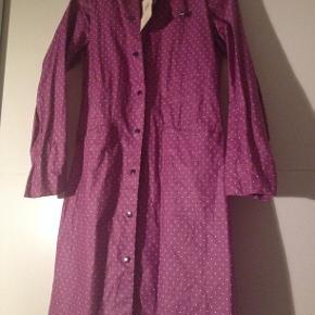 Flot Noa Noa regnjakke / frakke i lilla med hvide prikker. Med blød bomuldsrib i ærmerne, så den slutter til hvis det blæser. Lukkes nemt med trykknapper. Nypris 800 kr