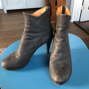Har brugt disse få gange, men der nogle mærker under den ene støvle (ses kun hvis man vender bunden i vejret på støvletten) sælger dem, da jeg ikke længere kan gå i høje hæle. Hælen måler 10 cm yderst og 7,5 cm inderst men der er et plateau forrest på 2,5, så det svarer til en hælhøjde på ca 7,5 / 5 cm - de er normale i størrelsen - farven er  gråbrun