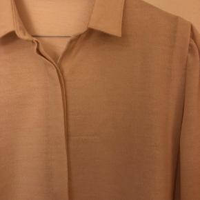 Beige vintage skjorte i uldblanding - derfor også lidt varm, at have på. Passer M-L. Mindre tegn på slid (se billede to)  Kan sendes eller afhentes i Aarhus N.