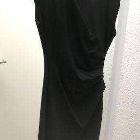 Tiger of Sweden MI STRETCH Kjole. Brugt 2 gange og fremstår næsten ubrugt. Klassisk sort kjole. Længde over knæ. Rynkedetaljer foran ved mave og bryst. Små ærmer der dækker skuldre. Lynlås i nakke. Yderstof er fast jersey med stræk - 70% Viscose/20% Polyamid/5% Elastane. Foer: 100% Polyester