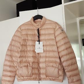 Moncler jakke ,rosa ,størrelse 5 (ca. 42) ,ny ,købt for stor . Nypris 4100 kr. Sælges for 2000 kr. tlf. 22329369