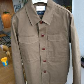 Flot overskjorte / jakke i workwear stilen lavet i økologisk bomuld. Fraven er en khaki / oliven nuance, sidste billede, model, er ikke repræsentativ for farven. Den er kun blevet båret indedøre, enkelte gange. Mp 375