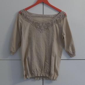En fin bluse i lysebrun, bomuld. Købt i Italien, kender ikke mærket. Fejler intet.  Kan hentes i Charlottenlund eller København.