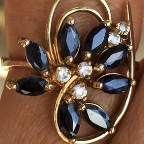 Brand: Guld Ring m. Safirer Varetype: Guld Ring m. Safirer Størrelse: 56 Farve: Guld/Blå   Flot og Meget Speciel 10 Karat Guld Ring m. 8 Ovale Midnats Blå Safirer på i alt 0,75 carat, Prydet m. 5 Små Diamanter i Accent i Midte.  Kvittering Medfølger  Guld : 10 Karat  Safirer i alt : 2 Stk.  Safirers Carat i alt : 0,50 carat  Safirers Farve : Midnatsblå   Diamanter i alt : 5 Stk.  Diamanters Carat : Accent  Diamanters Kvalitet : I1 - I2  Diamanters Farve : I - J  Ringens Bredde i Front : 17 mm x 17 mm på Bredeste Sted  Ringens Bredde i Bund : 3 mm  Ringens Vægt : 3,3 g  Ringens Str. : 56