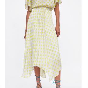 Plisseret nederdel med blødt fald. Med asymmetrisk sømkant, matchende for og lynlåslukning i sidesømmen.  Str. L. Aldrig brugt. Mærke sidder stadig på. Nypris: 299kr.
