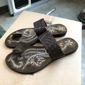 Ubrugte. Flotte håndsyet mørk brune sandaler med tå split. Der står str. 37 på dem,  jeg passer sem og er str. 38. Sender gerne, mod betalt porto.