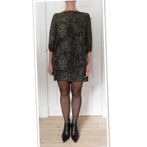 Bytter ikke! Mp. 500,-eksklusiv porto. Købspris kr. 1.900,- Fremstår som ny. Brugt en enkelt gang. Elegant kjole i smukt stof fra Sand str. 38, (M) Kjolen kan bruges som en cocktailkjole, festkjole eller til alm. brug. Let gennemsigtigt yder stof, men kjolen har en underkjole. Lynlås, 25 cm, ned midt bag. 3/4 ærmer, med elastik i kanten. Yderstof: 25% Silke, 75% Viskose. Underkjole: 100% Polyester. Farve: farven er i flaskegrønne nuancer, farven afhængig af lyset. I sol bliver farven mere varm grøn. SAND Copenhagen størrelsesguide str. 38: Bryst mål 90 cm Talje mål 75 cm Hofte mål 99 cm Kjolens mål: Længde fra skulder 84 cm. For og ryg stykke målt ved bryst linjen 102 cm, fra sidesøm til sidesøm. Modellen på billederne er en str. 38, bryst mål 92 cm, hofte mål 102 cm. Kommer fra et ikke ryger hjem. Hænger i dragtpose. Bruger ingen parfume.